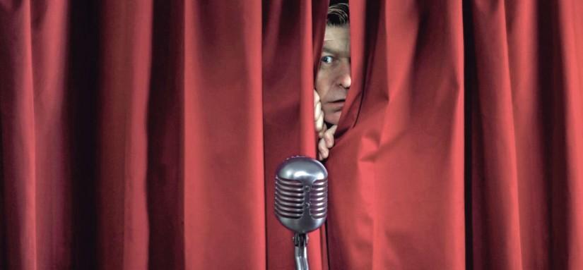 apresentador escondido atrás da cortina